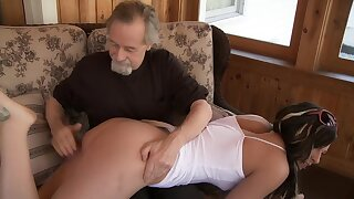 Older man bends over a sexy chick over his knees upon spank her ass